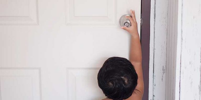 Small child reaching for door handle
