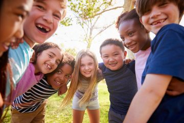 Group of kids outside in a circle smiling