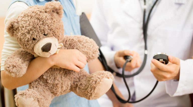 Clinician with patient holding a bear