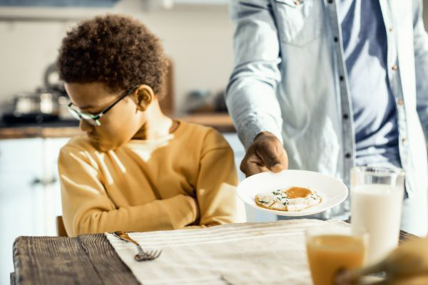 young boy refusing a plate of food from his father