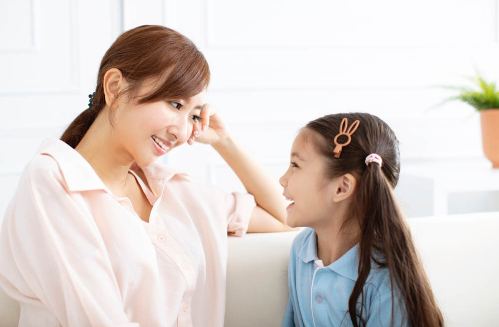 mother and young daughter talking and smiling