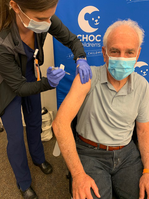 Older man receiving a COVID-19 vaccination