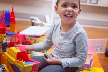Boy plays while receiving Batten Disease treatment