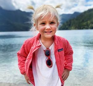 Jax smiling with blonde pigtails wearing pink coat in front of mountain scenery